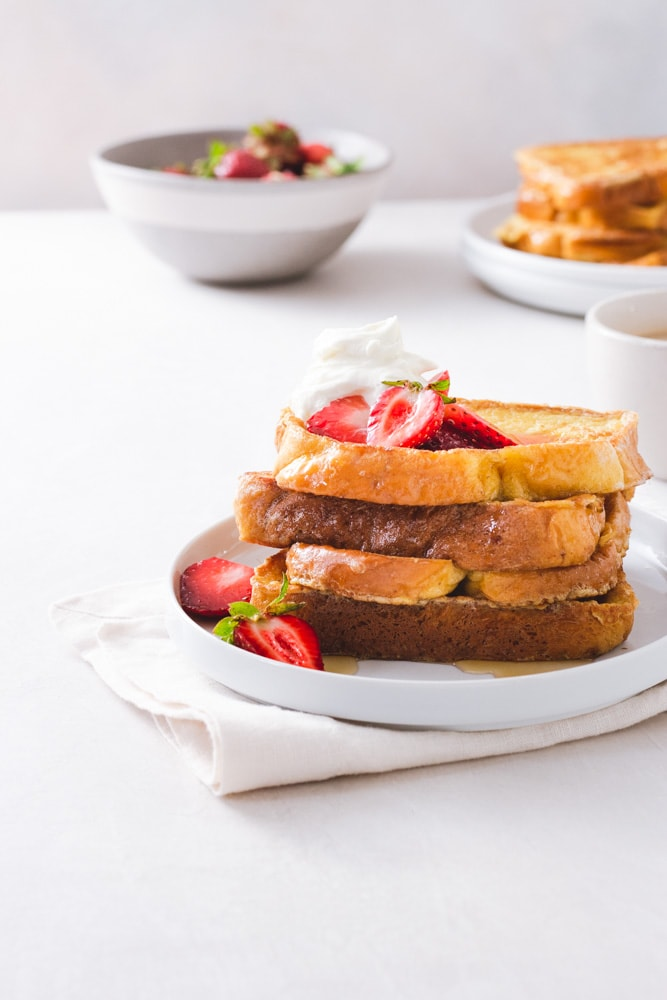 Straight on view of a stack of Brioche French Toast topped with macerated strawberries and whipped mascarpone cream on a white plate on a napkin on a white surface with strawberries, a cup of coffee, and a plate of more French toast in the background.