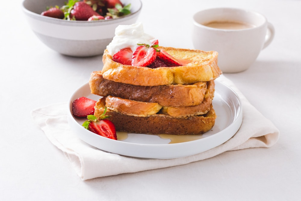 Straight on view of a stack of Brioche French Toast topped with macerated strawberries and whipped mascarpone cream on a white plate on a napkin on a white surface with a cup of coffee and bowl of strawberries in the background.