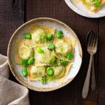 Overhead image of a rustic ceramic plate with fava bean and ricotta ravioli in brown butter sauce with whole fava beans, mint and parmesan cheese on top surrounded by rustic silverware (fork and spoon), a biege dish towel and another plate of pasta on a dark wood surface.