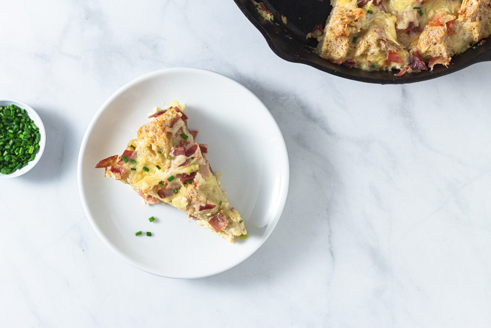 Overhead shot of a slice of Ham and Cheese Strata made with Bayonne Ham on a marble surface surrounded by a small bowl of chopped chives and the remainder of the strata in a cast iron pan.