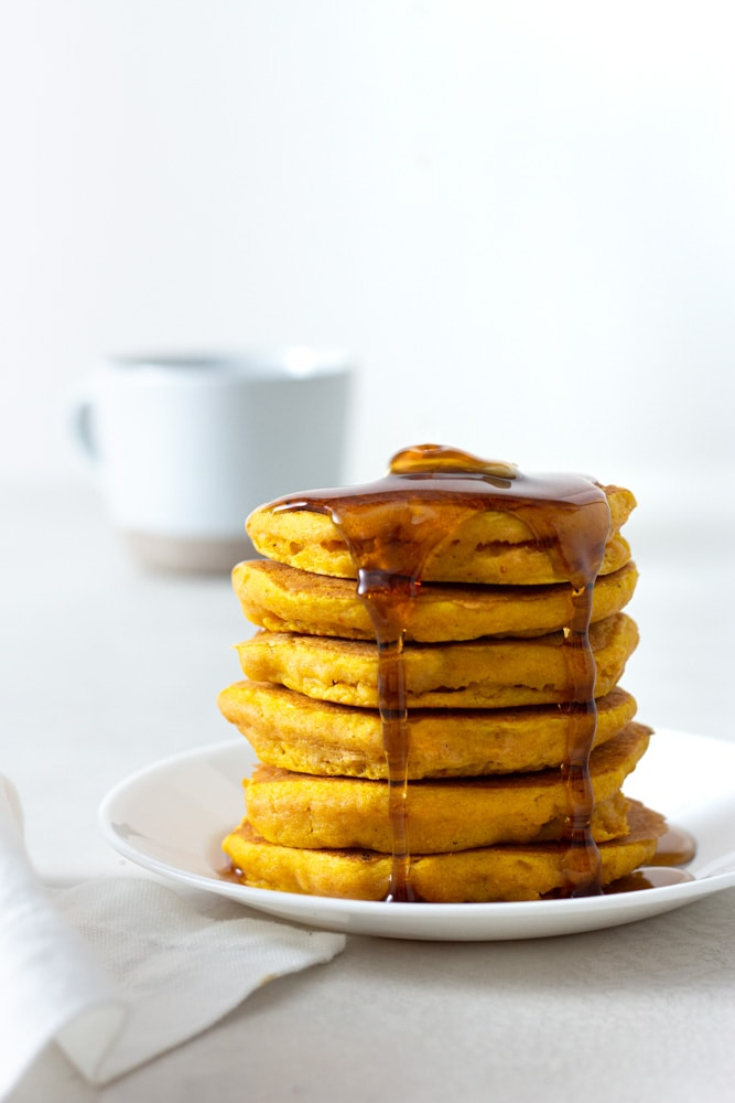 Straight on shot of a stack of pumpkin pancakes with butter and maple syrup with a cream and white background.