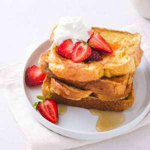 Brioche French Toast with Strawberries and Mascarpone Cream stacked on a plate.
