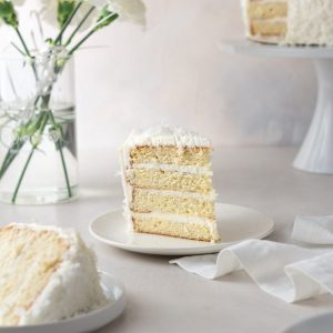 A tall slice of coconut layer cake on a plate next to white flowers and the rest of cake.