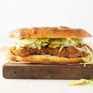 Pork Schniztel Sandwich with Apple Brussels Sprout Slaw on a wooden cutting board.