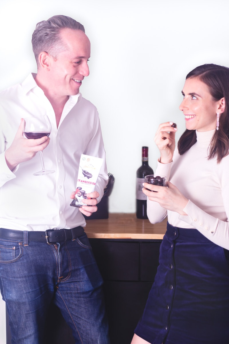 A couple looking towards each other holding red wine and Lamontagne Chocolate wearing going out clothes.