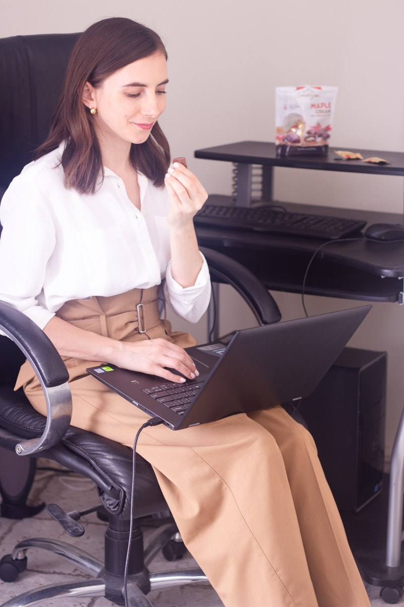 A brunette girl holding a Maple Cream Lamontagne Chocolate wearing work clothes, sitting on a desk chair and looking at a laptop.