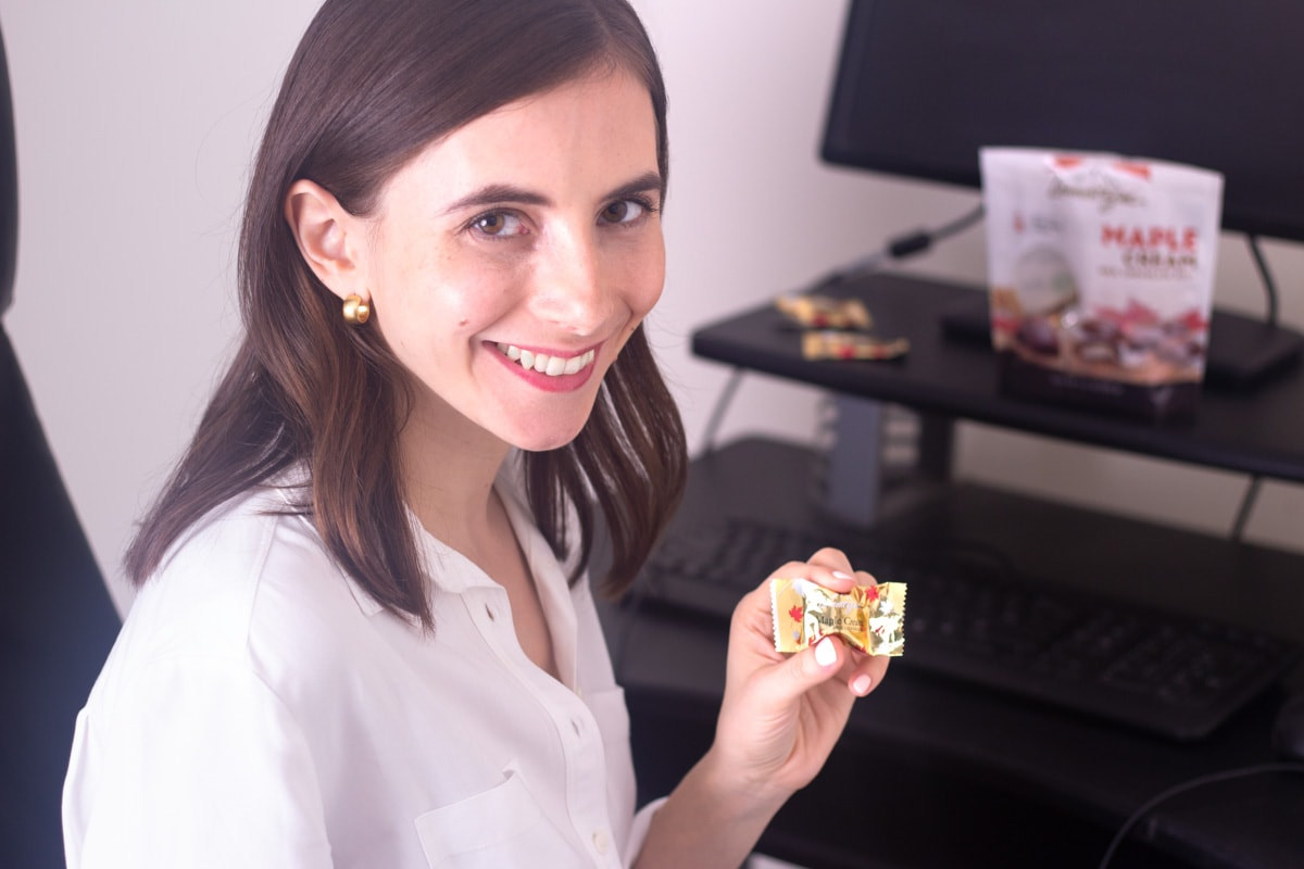 A brunette girl holding a Maple Cream Lamontagne Chocolate wearing work clothes with a computer desk in the background.