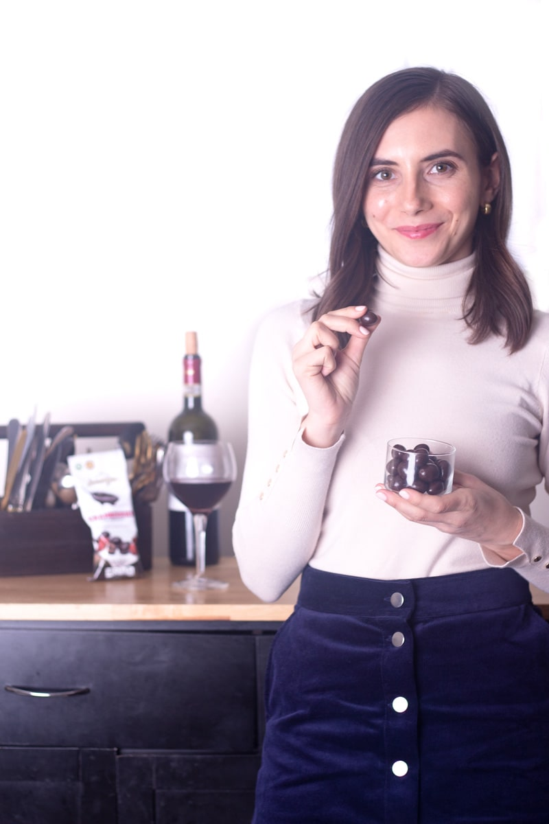 Straight on photo of a brunette girl holding a glass cup of chocolate covered cranberries from Lamontagne brand.
