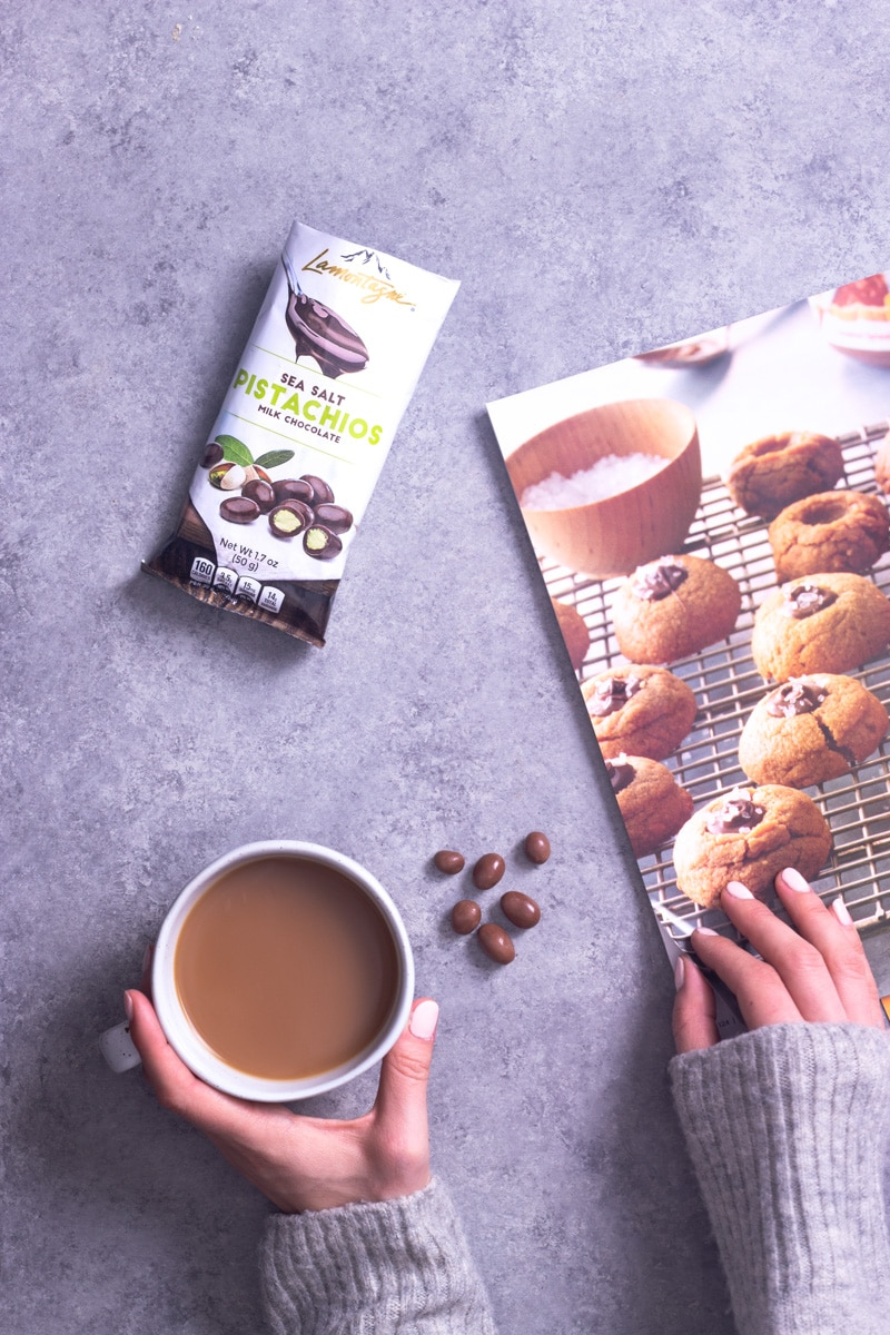 Overhead view of hands in a grey sweater holding a cup of coffee and flipping through a baking magazine with Lamontagne chocolate covered pistachios on the table.