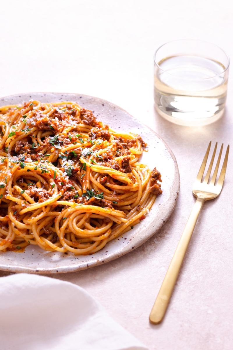 Angled, close up shot of a plate of spaghetti bolognese topped with parsley and parmesan cheese on a light, rustic surface next to a gold fork, cream napkin and glass of white wine.