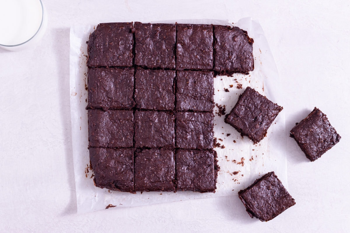 Overhead view of healthy brownies cut into squares on parchment paper next to a glass of milk on a white surface.