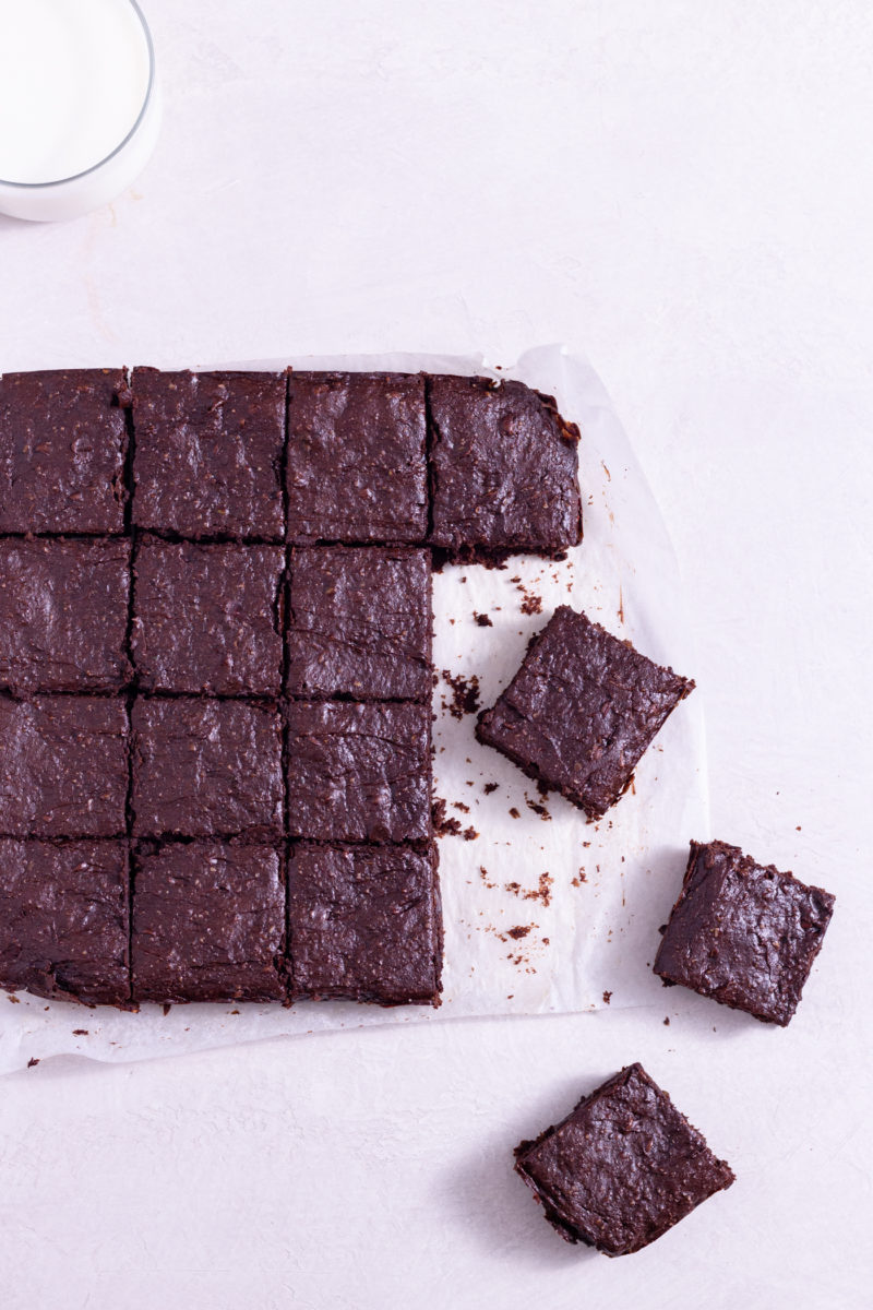 Overhead view of Avocado Brownies cut into squares on parchment paper next to a glass of milk on a white surface.