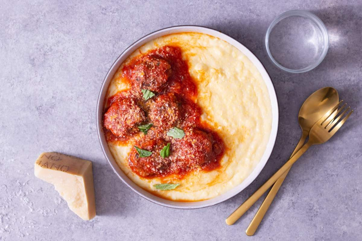 Overhead view of a bowl of polenta topped with meatballs in tomato sauce cooked in pressure cooker next to a glass, gold utensils, and a hunk of parmesan on a light grey surface.