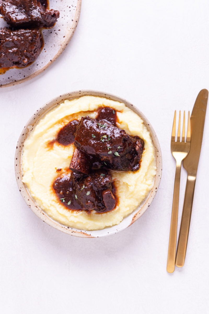 Overhead view of a shallow bowl of mashed potatoes topped with  Short Ribs made in a pressure cooker with a red wine tomato sauce next to copper utensils on an off white surface.