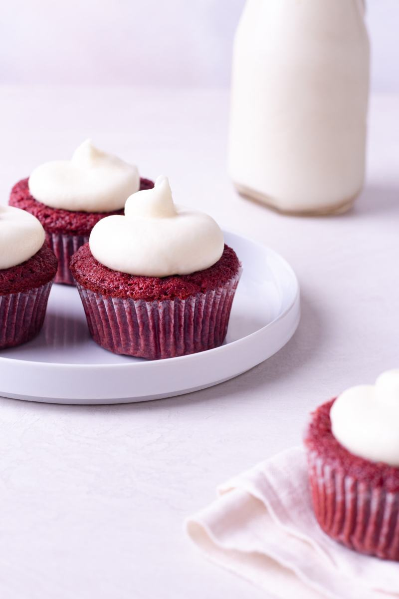 Straight on view of a plate of red velvet cupcakes with cream cheese frosting with a jug of milk in the background.