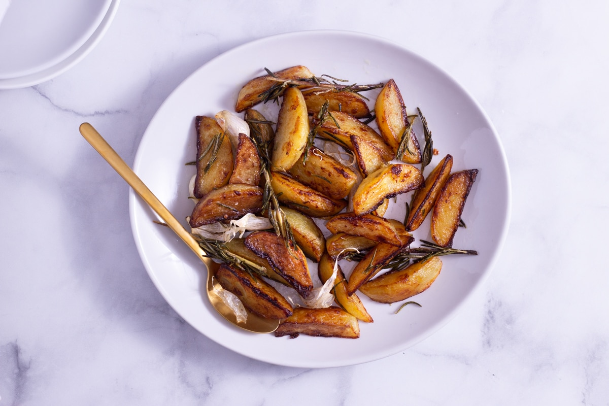 Overhead view of potato wedges with rosemary on a white platter with a gold spoon on a marble surface next to white serving plates.