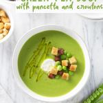 Overhead view of a bowl of green pea soup topped with pancetta, croutons and creme fraiche.