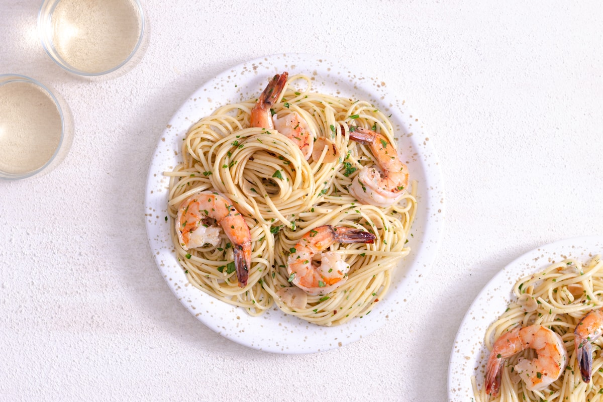 Overhead view of a plate of shrimp pasta surrounded by a wine glass on a white plaster surface.