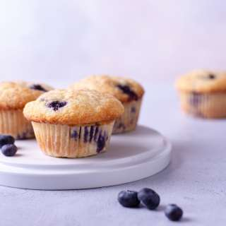 Straight on shot of a plate of Lemon Blueberry Muffins with a light blue background.
