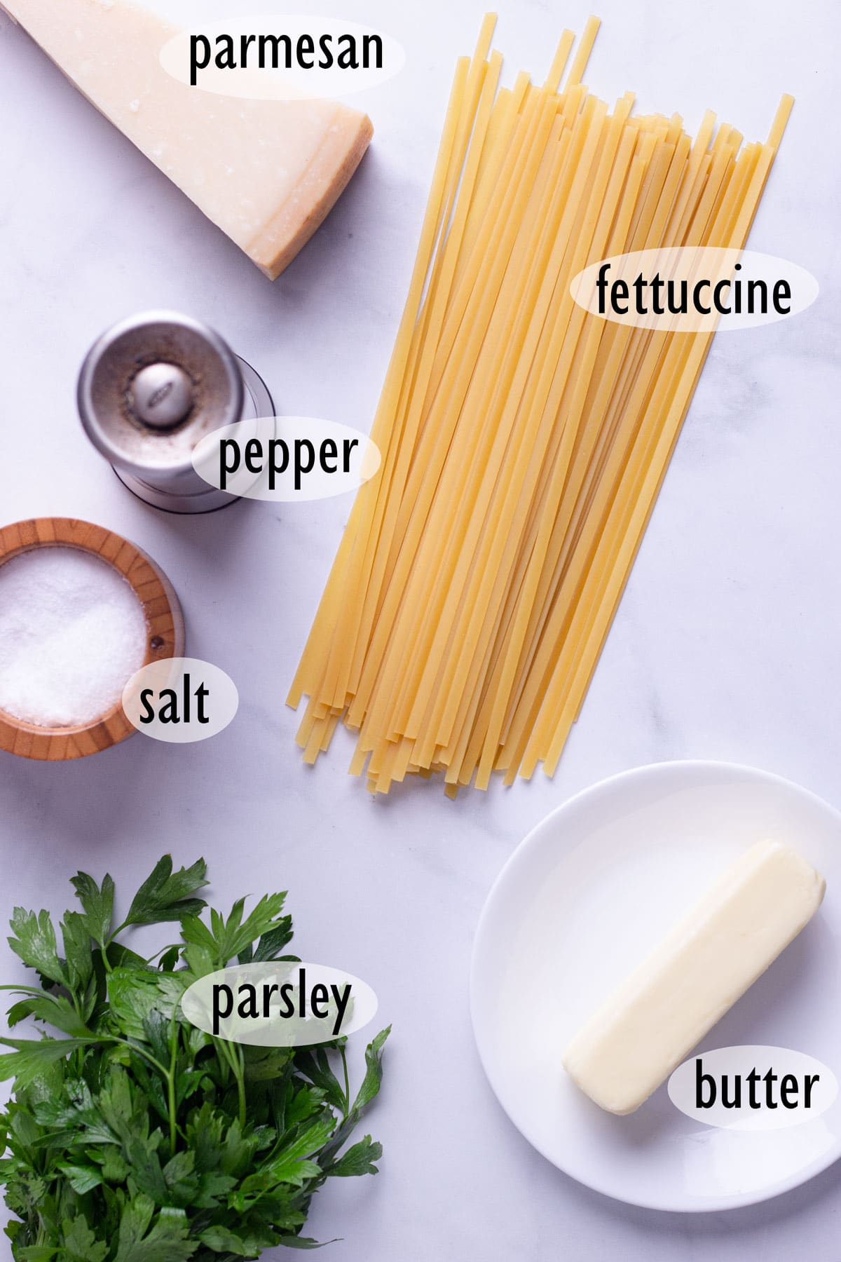 Ingredients used for pasta dish including fettuccine, parmesan cheese, butter and parsley.