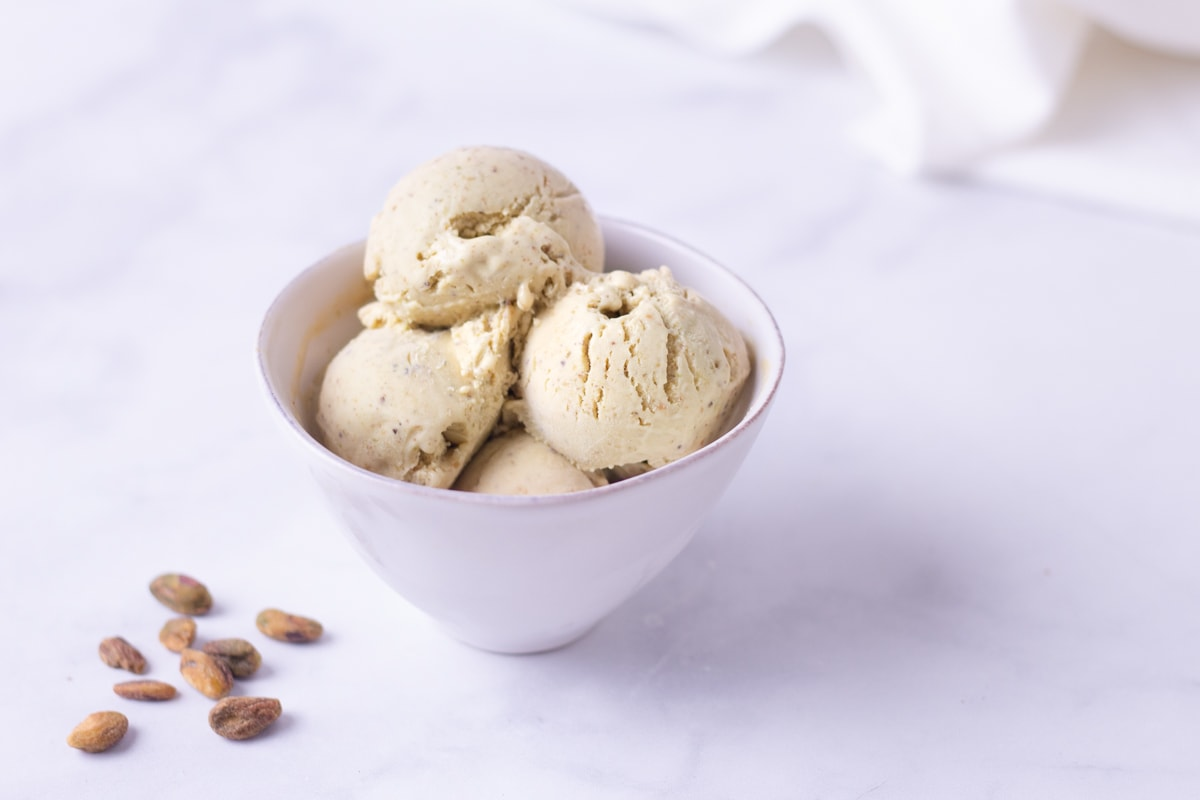 Angled view of a bowl of ice cream with scattered pistachios on a marble surface.