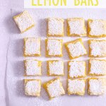 Overhead, zoomed out view of cut lemon bars on parchment.