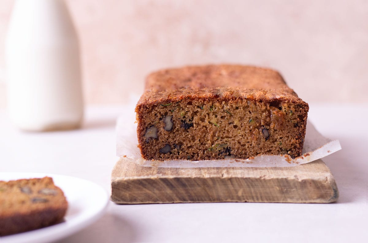 Straight on shot of almond flour zucchini bread on a cutting board near a jug of milk and slice of bread on a plate.