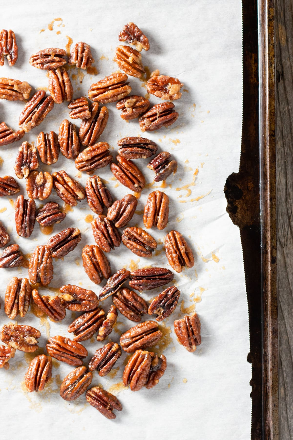 Maple Butter Pecans on a baking sheet lined with parchment.
