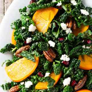 Closeup of a platter of salad with kale, pomegranates, persimmons, pecans and feta.