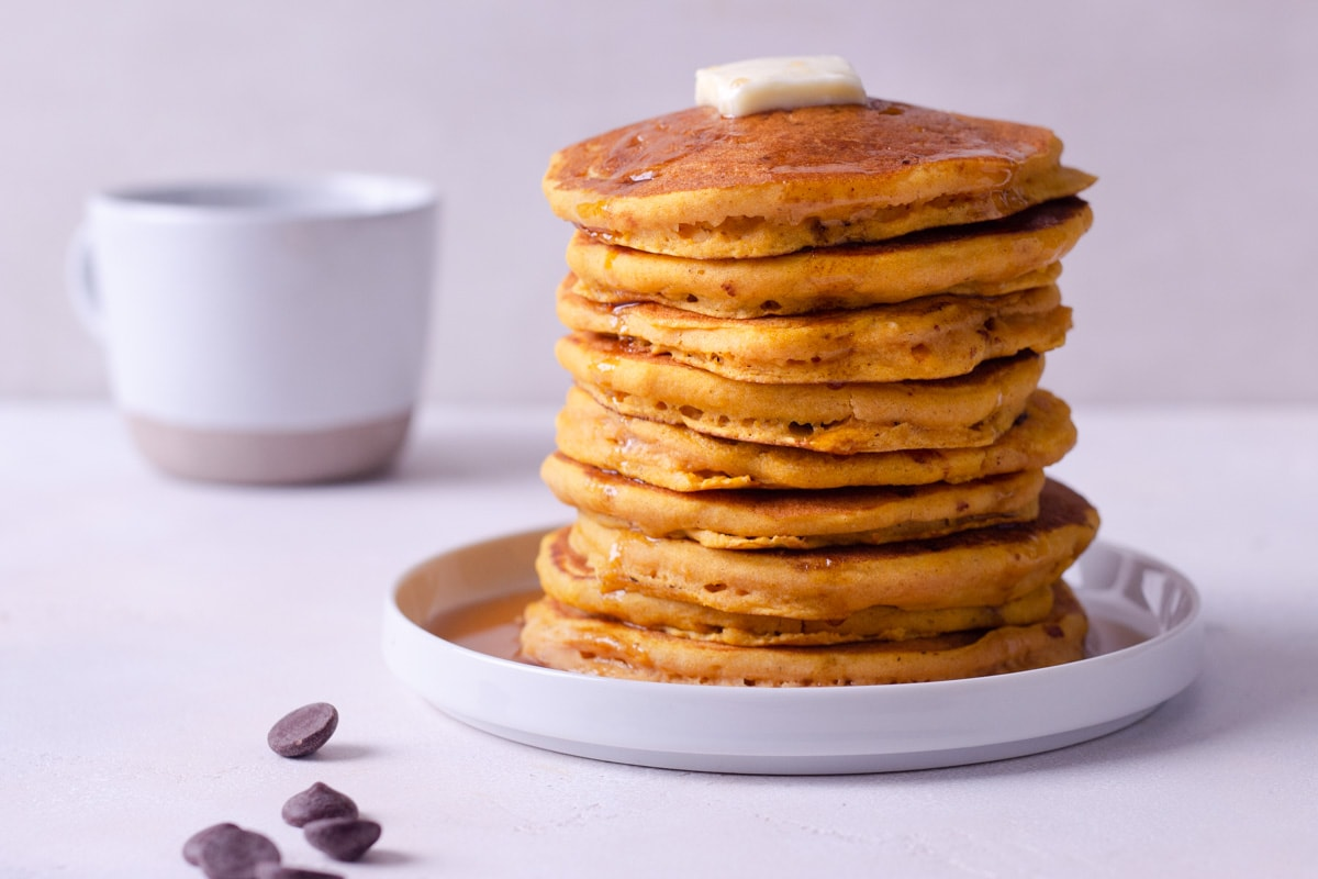 Straight on view of a stack of pumpkin pancakes on a plate, surrounded by scattered chocolate chips with a coffee mug in the background.