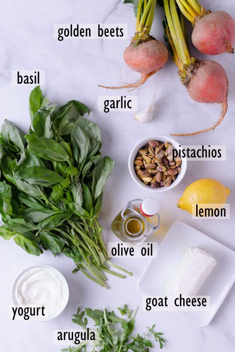 Ingredients for salad including beets, pistachios, basil, lemon, goat cheese, yogurt, arugula and olive oil