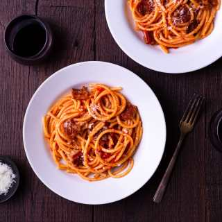 Overhead view of two bowls of pasta with fresh tomato sauce and guanciale surrounded by glasses of red wine and a bowl of pecorino cheese.