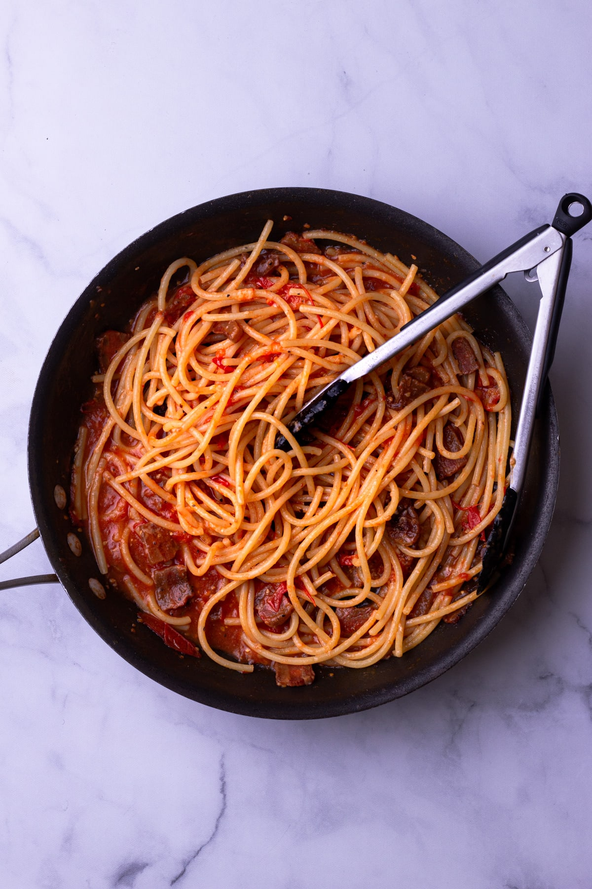 Overhead view of a pan with pasta and tomato-guanciale sauce with tongs on a marble surface.
