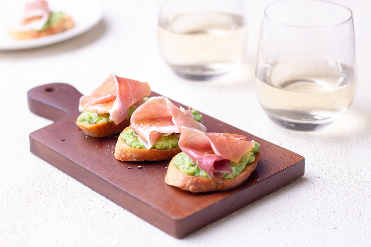 Pea and Ricotta Crostini topped with prosciutto on a small wood cutting board over a textured surface surrounded by glasses of white wine and a plate in the background.