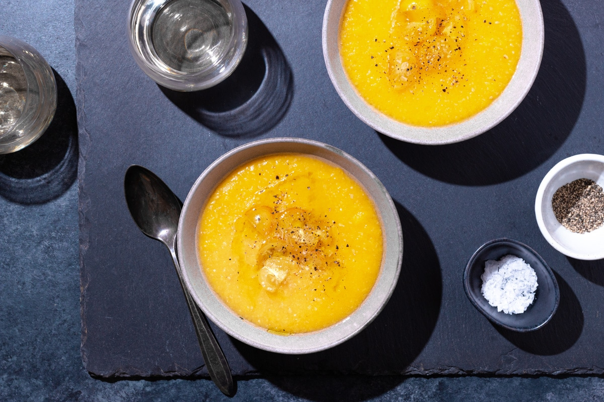 Overhead view of two bowls yellow tomato gazpacho surrounded by glasses of wine, salt and pepper pinch bowls, and a spoon on a slate surface.