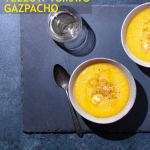 Overhead view of two bowls of yellow gazpacho and a grey-blue surface surrounded by glasses of white wine, crusty bread, a spoon and salt and pepper bowls.