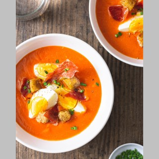 Two bowls of salmorejo gazpacho soup topped with eggs and serrano ham on a wood surface.