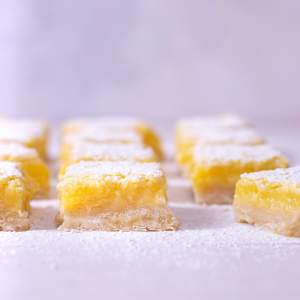 Straight on view of rows of lemon bars on a light surface.