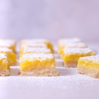 Straight on shot of rows of lemon bars on a light surface.