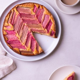 Cake top with rhubarb in chevron pattern on a cream surface next to a cup of coffee and slice of cake.