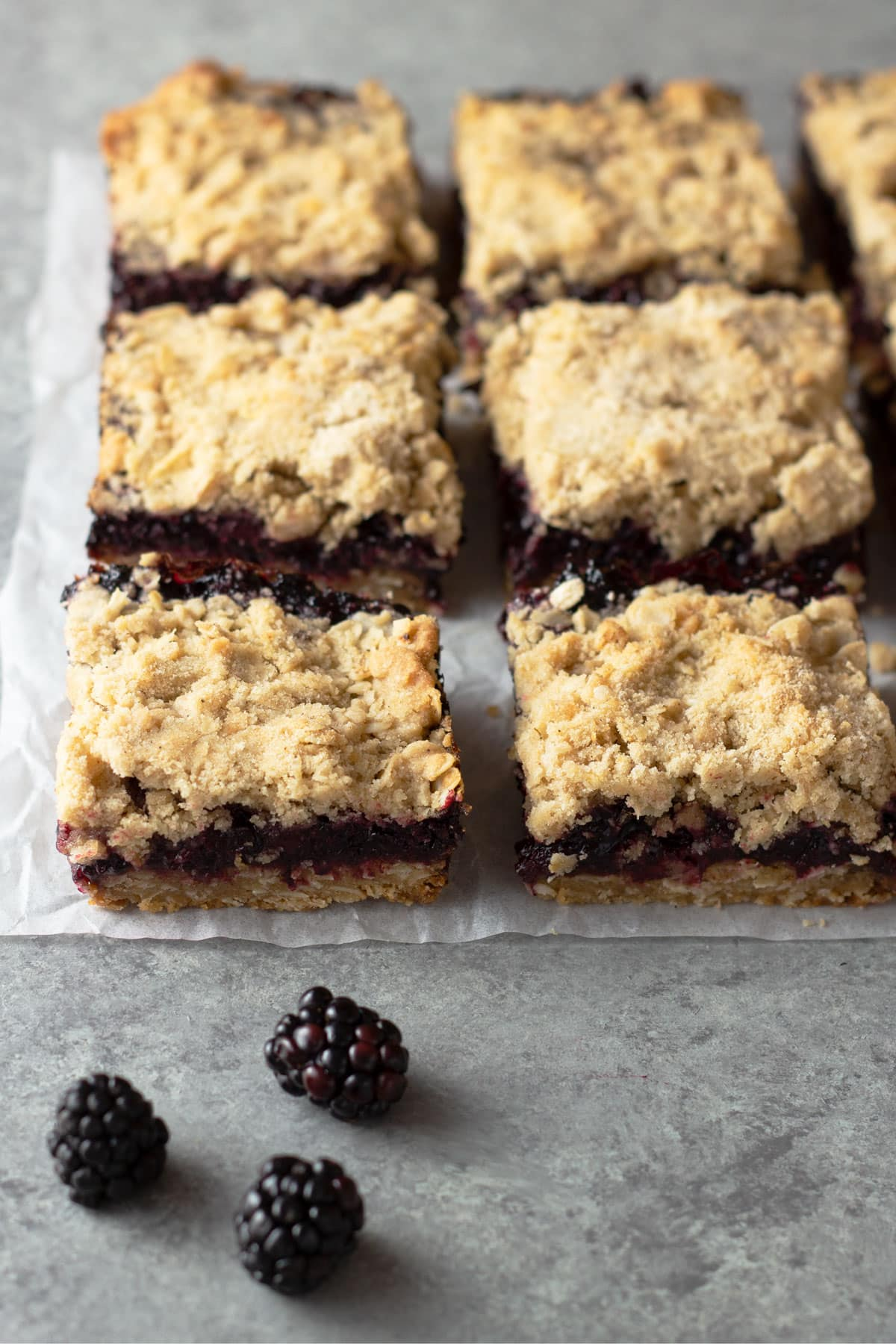Angled view of a group of squares of blackberry bars on parchment on a grey surface.