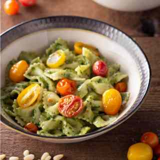 Angled view of a bowl of farfalle pasta with pesto sauce and roasted tomatoes on a wood surface.