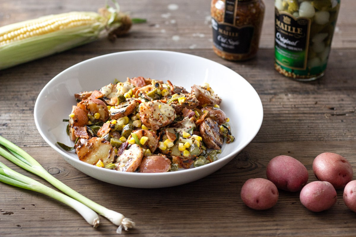 A bowl of Grilled Potato Salad with corn, bacon, and scallions on a wood surface surrounded by raw ingredients.