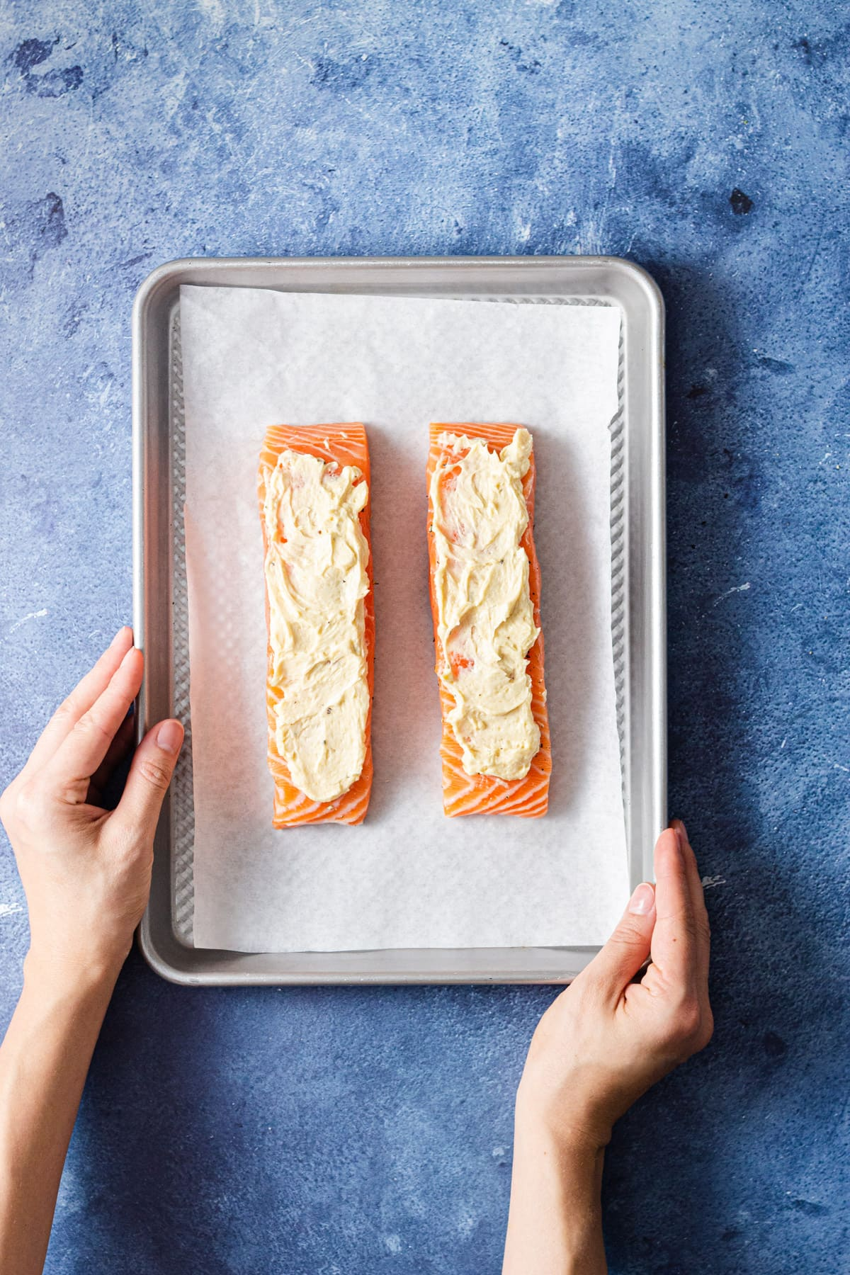 Overhead view of a sheet tray with raw salmon rubbed with miso butter on a blue background.
