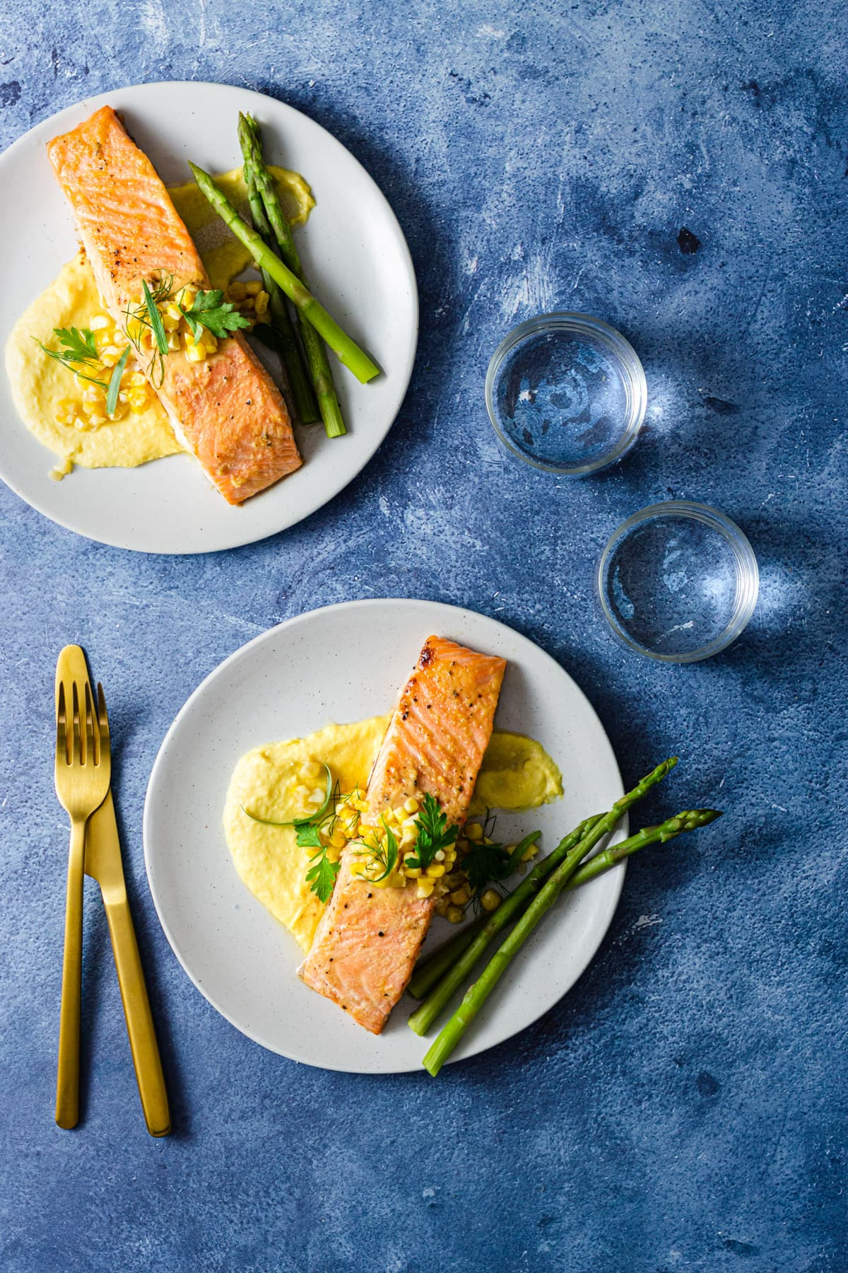 Two plates of Miso Butter Salmon over Corn Puree next to asparagus on light grey plates with a vibrant blue background next to water glasses and utensils.