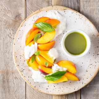 Overhead view of a plate of peach and burrata salad with fresh basil leaves and a cup of basil oil.