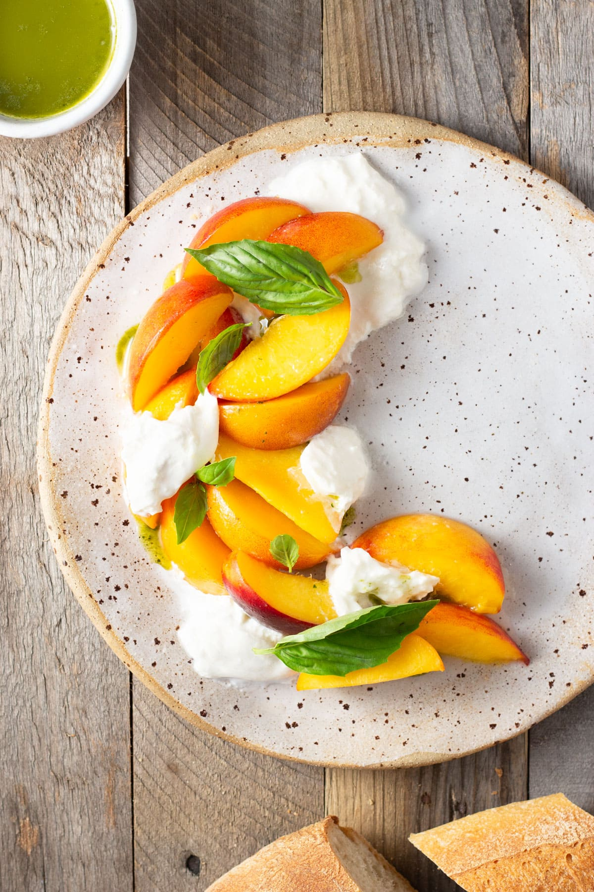 Overhead view of a rustic plate topped with sliced peaches, chunks of burrata cheese and fresh basil leaves with a cup of basil oil in the corner.