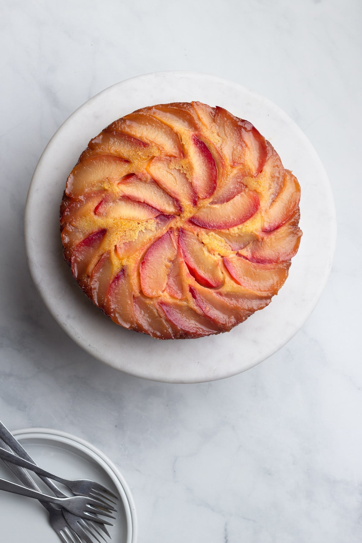 Overhead view of a Polenta Plum Upside Down Cake on a marble cake stand on a marble surface with serving dishes and forks in the corner.