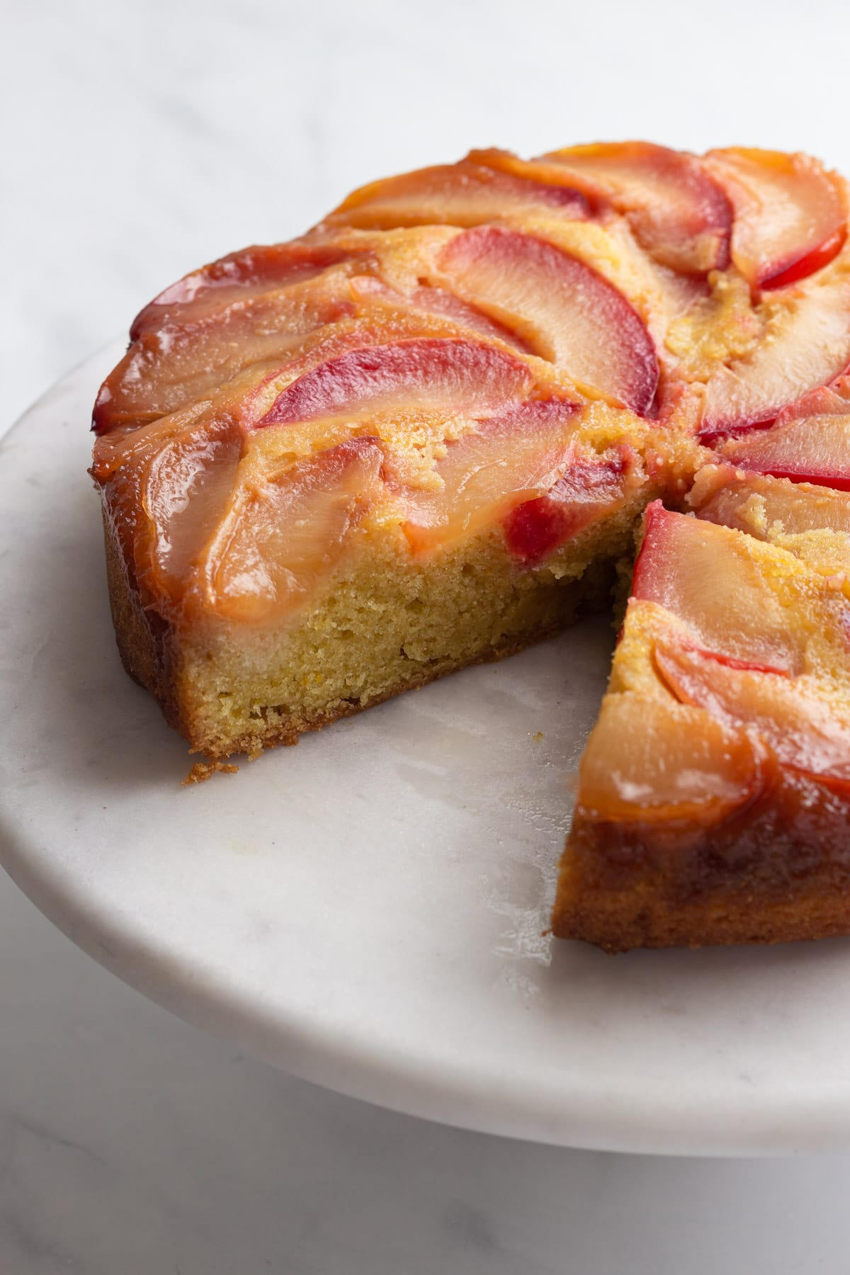 Closeup slightly angled view of a sliced plum cake revealing the cornmeal interior on a marble cake stand.