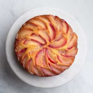 Overhead view of a Polenta Plum Upside Down Cake on a marble cake stand on a marble surface.